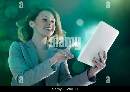 Young woman digital tablet and light on finger - Stock Photo