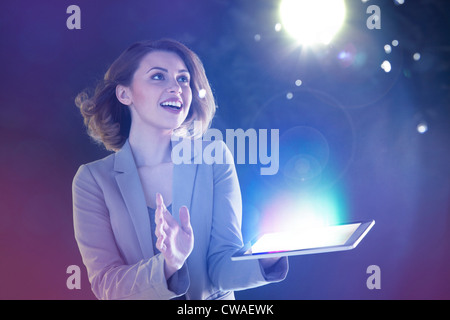 Young woman looking at lights coming from digital tablet - Stock Photo