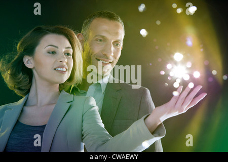 Businesspeople reaching out to lights - Stock Photo