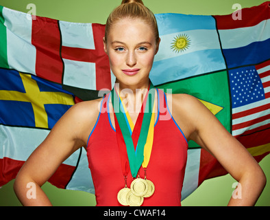 Young woman in front of international flags wearing medals - Stock Photo