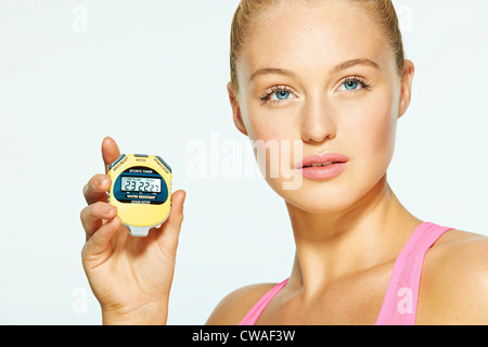 Young woman holding stop watch - Stock Photo