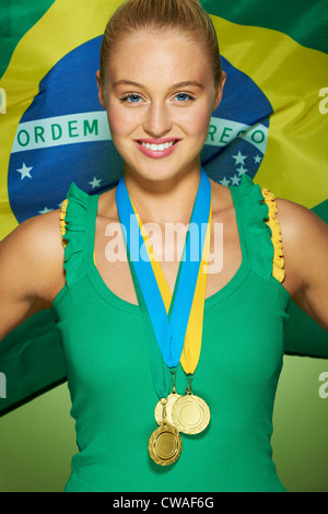 Young woman in front of Brazilian flag with medals - Stock Photo