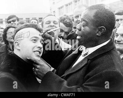 Louis Armstrong (1901-1971), African American Jazz musician, drawing a trumpet and autographing the side of a young man's head Stock Photo