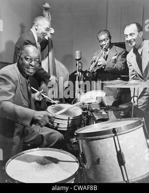 Louis Armstrong (1901-1971), playing trumpet with others during a 1947 broadcast of 'This is Jazz' radio show, directed by Rudi Stock Photo