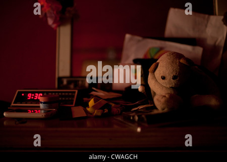 Digital alarm clock and toys on bedside table - Stock Photo