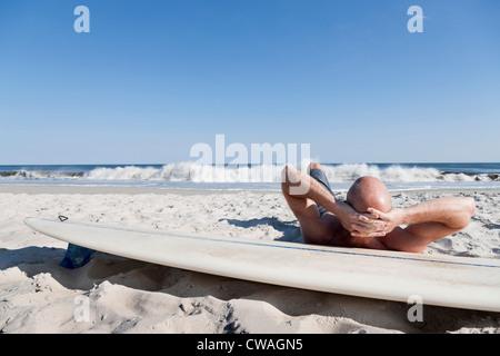 Surfer lying on surfboard on beach