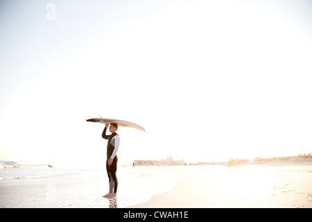 Surfer carrying surfboard on head - Stock Photo