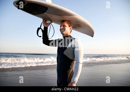Surfer carrying surfboard on head