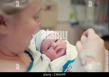 Mother cradling newborn baby girl - Stock Photo