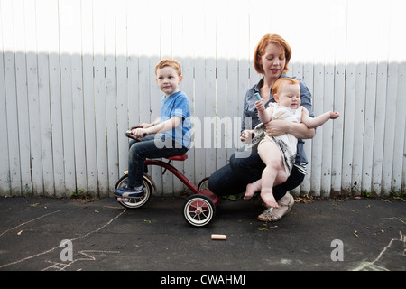 Mother playing in yard with two children - Stock Photo