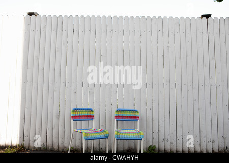 Two chairs by fence - Stock Photo