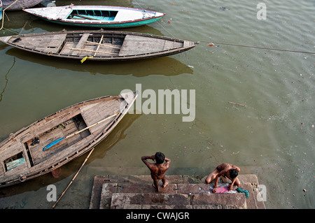 Young men bathing and washing in the ghats of the river Ganges. Varanasi, India - Stock Photo