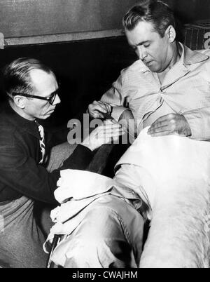 Prop man Bill Sapp screws James Stewart into a plaster cast on the set of Alfred Hitchcock's 'REAR WINDOW', 1954. - Stock Photo