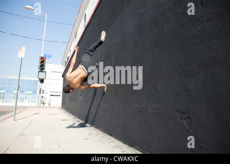 Man running up wall, demonstrating parkour - Stock Photo