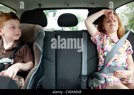Girl making faces in car with little brother - Stock Photo