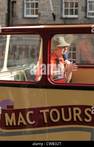 'Mac Tours' tour guide on an open top tour bus. - Stock Photo
