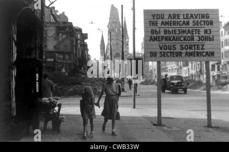 Berlin, Germany with sign indicating the end of the American sector in the foreground and the Kaiser Wilhelm church - Stock Photo