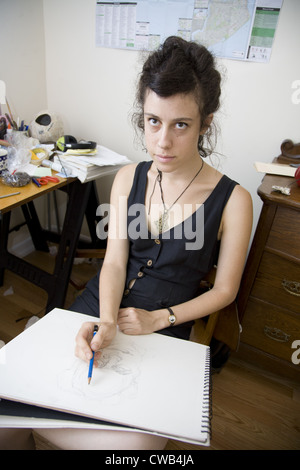 Young artist sketching someone in her studio in Brooklyn, NY. - Stock Photo