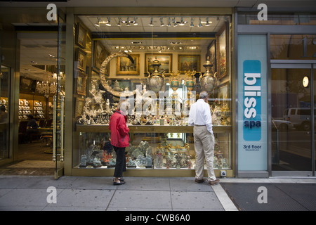 People admiring the pieces displayed at an antique dealer along 57th Street in Manhattan - Stock Photo