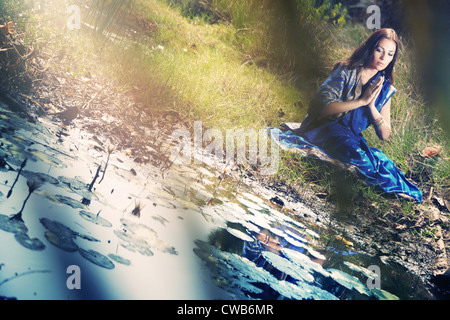 Single lady in traditional Indian sari sitting at the pond and praying - Stock Photo