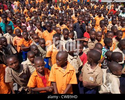 Rwandan school children stand in their playground waiting for instructions - Stock Photo