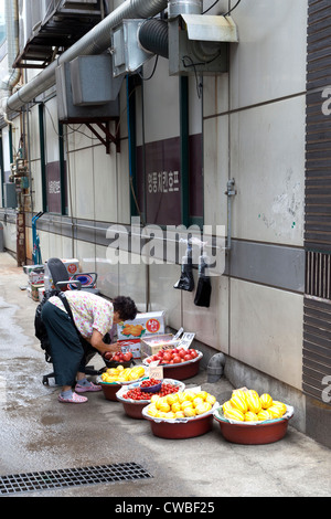 A Korean woman sells fruit and vegetables by a building on a sidewalk near Seoul, Korea. - Stock Photo
