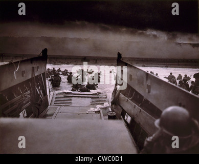 American soldiers wade from Coast Guard landing craft toward the Omaha Beach against machine gun fire on D-Day. - Stock Photo