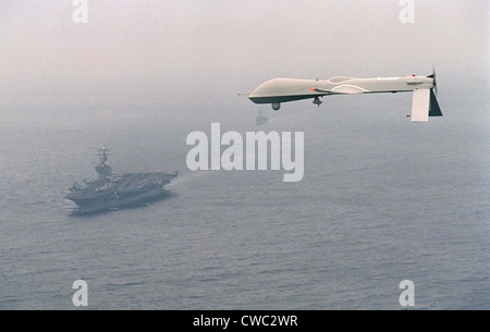 Predator Unmanned Aerial Vehicle flies above the aircraft carrier USS Carl Vinson on a Navy aerial reconnaissance - Stock Photo