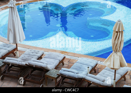 Sun loungers around a swimming pool in a tropical resort - Stock Photo