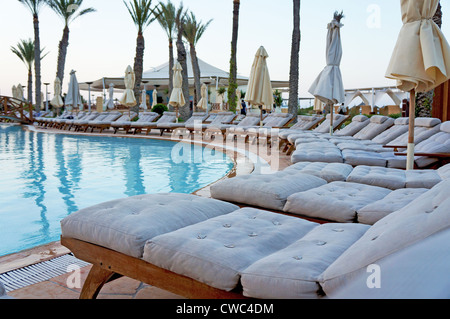 Row of empty sun loungers around a resort swimming pool - Stock Photo