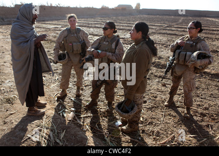 U.S. Marines in Afghanistan assigned to a female engagement team speak with a local Afghan man in his compound during - Stock Photo
