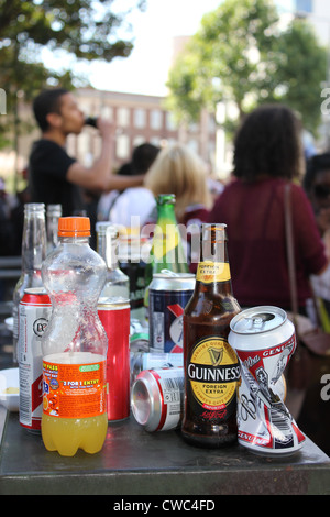 Table with empty bottle and drink cans littering streets - Stock Photo