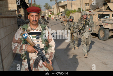 An Iraqi soldier leads the way during a search operation with US Army soldiers in the Rusafa area of Baghdad Iraq - Stock Photo