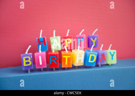 Unlit birthday candles over colored background - Stock Photo