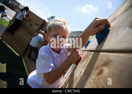 A young boy climbs on a climbing wall UK - Stock Photo