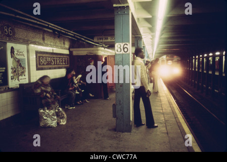New York City Subway. Passengers wait on a subway platform on the Lexington Avenue line at 86th Street as a train - Stock Photo