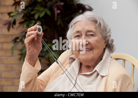 An elderly woman shows off her emergency call pendent UK - Stock Photo
