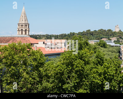 A view of a church steeple in Nimes, France, with the Tour Magne in the distance - Stock Photo