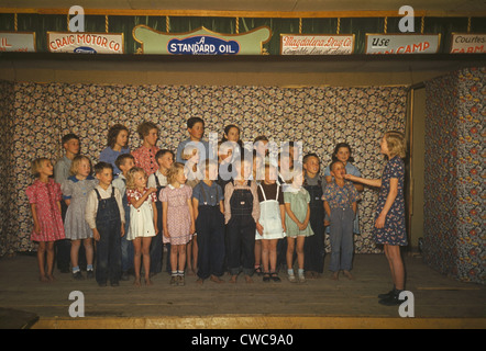 School children some barefoot singing on a stage Pie Town New Mexico. The stage curtain posts advertisements from - Stock Photo