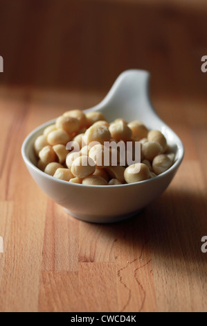 Macadamia Nuts in bowl - Stock Photo