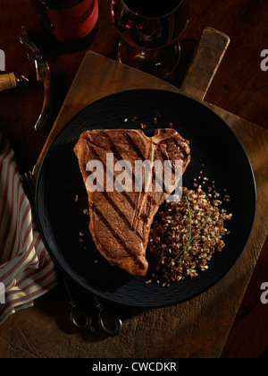A grilled t-bone steak plated with quinoa grains and red wine. - Stock Photo
