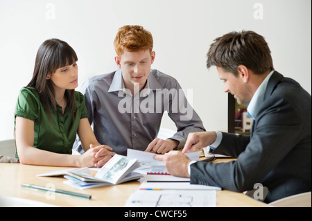 Real estate agent discussing property documents to his clients - Stock Photo