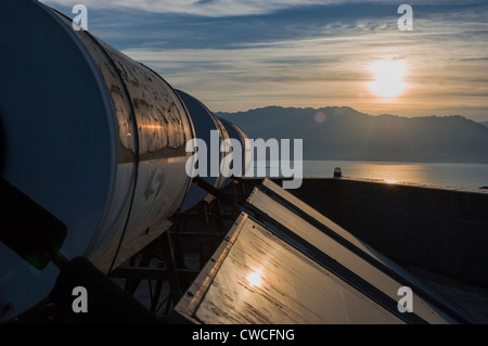 An array of solar water heaters (tanks and collector panels) on roof of an apartment building, Israel - Stock Photo