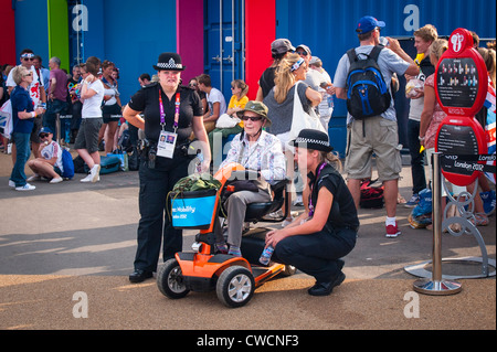 London 2012 Stratford Olympic Park two policewomen female police officers chat to help elderly lady in wheelchair in hat
