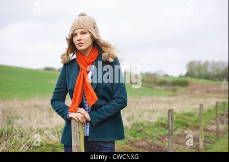 Beautiful woman standing in a field - Stock Photo
