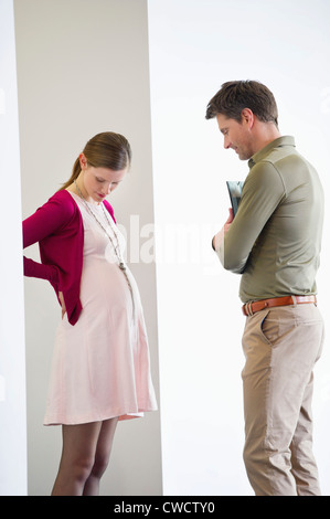 Man looking at a pregnant woman - Stock Photo
