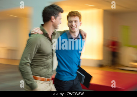 Businessmen walking with their arm around each other in an office corridor - Stock Photo