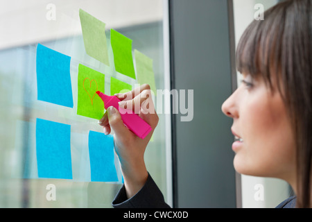 Businesswoman drawing heart shape on an adhesive note in an office - Stock Photo
