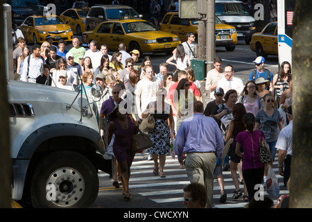 Hot summer day on the always crowded 5th Avenue in Midtown Manhattan, NYC. - Stock Photo