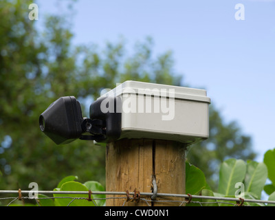 A small CCTV security camera mounted on a fence post in a rural area. - Stock Photo